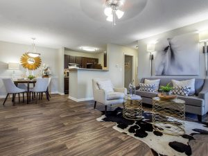 Furnished living room with ample seating, ceiling fan, and view of dining area at The Laurel apartments for rent