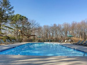Outdoor swimming pool with sundeck, lounge chairs, and umbrellas at The Laurel apartments for rent