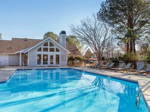 Outdoor swimming pool with sundeck and lounge chairs at The Laurel apartments for rent