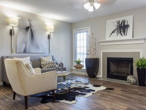 Spacious living room with ample seating, ceiling fan, and fireplace at The Laurel apartments for rent