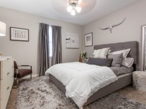 Furnished bedroom with ceiling fan and large window for natural light at The Laurel apartments for rent