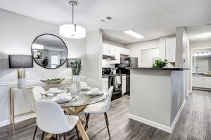 Dining area with four place settings and view of kitchen at The Laurel apartments for rent