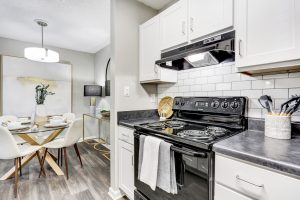 Kitchen with black appliances, white cabinetry, and view of dining area at The Laurel apartments for rent