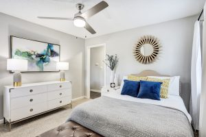 Furnished bedroom with ceiling fan and art work at The Laurel apartments for rent