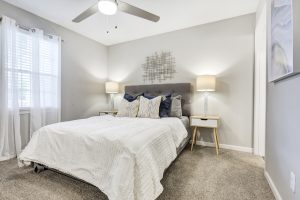 Furnished bedroom with ceiling fan and window for natural light at The Laurel apartments for rent