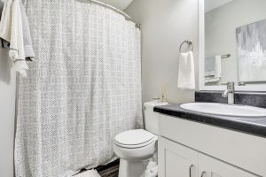 Bathroom with shower/tub combo, toilet, towel rack, and vanity at The Laurel apartments for rent