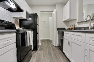 Kitchen with black appliances, white cabinetry, and storage closet at The Laurel apartments for rent