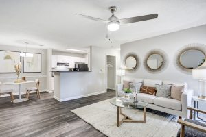 Open-concept living room with ample seating, lighting, and view of kitchen and dining room at The Laurel apartments for rent