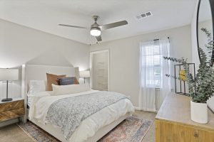 Furnished bedroom with ceiling fan, window for natural light, and walk-in closet at The Laurel apartments for rent