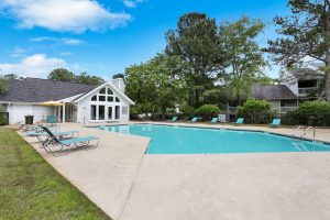 Outdoor pool with umbrellas and lounge chairs at The Laurel apartments for rent in Spartanburg, SC