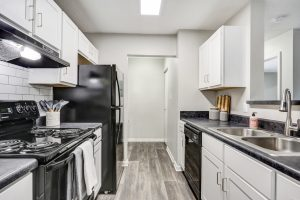 Kitchen with black appliances, white cabinetry, and ample storage at The Laurel apartments for rent